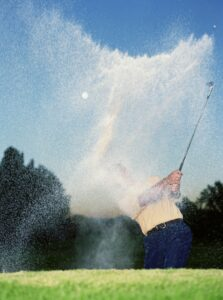 Image of man playing golf on golf ball injuries blog